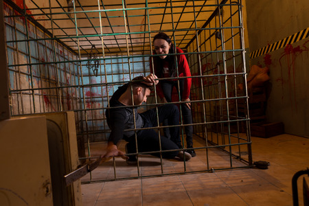 imprisoned: Two young Halloween victims imprisoned in a metal cage with a blood splattered wall behind them, boy pulling his hand through the bars and trying to get out
