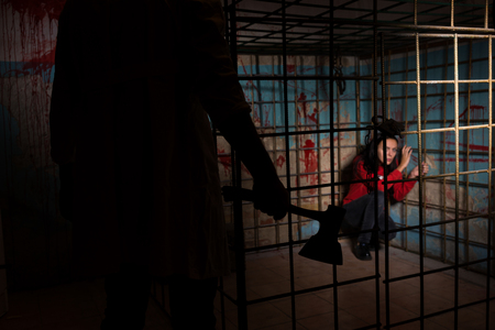 ghoulish: Shadowy male figure holding an ax in front of scared female victim imprisoned in a metal cage with a blood splattered wall behind her sitting in terror awaiting a fate Stock Photo