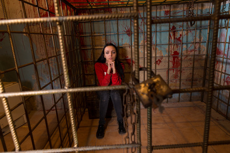 fate: Young female victim imprisoned in a metal cage with a blood splattered wall behind her sitting in terror awaiting a fate Stock Photo