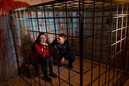 fate: Couple of frightened Halloween victims imprisoned in a metal cage with a blood splattered wall behind them sitting in terror awaiting their fate
