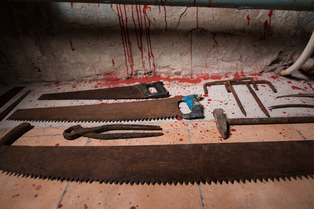 maniacal: Saws, sickles, hammer and other devices on the bloody floor in basement with pipes and wires in a Halloween horror concept