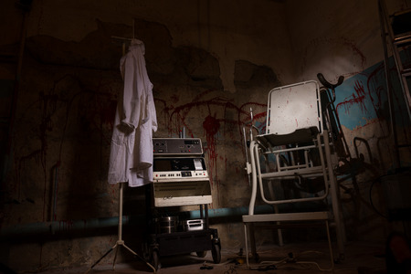 psychotic: View of electrical shocking device near medical gown hanging on the hanger and scary chair with blood stained wall for concept about torture or scary Halloween theme