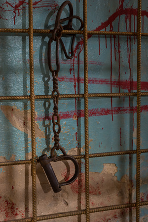 maniacal: Shackles hanging from chains on prison bar for concept about torture or scary Halloween theme Stock Photo