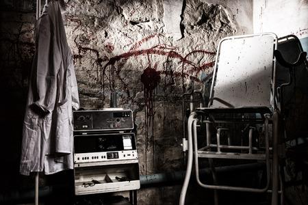 ハンガーと怖い椅子拷問または怖いハロウィーンのテーマについての概念の血の壁に掛かっている白いガウンに近い危険な電気衝撃的なデバイス