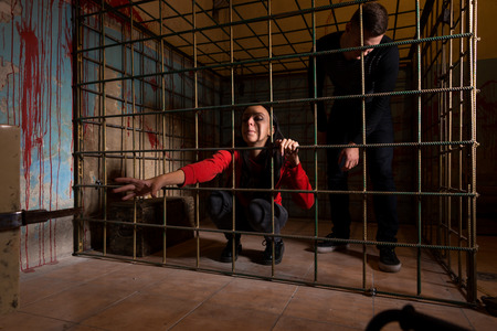 imprisoned: Victims imprisoned in a metal cage with a blood splattered wall behind them, girl pulling her hand through the bars and trying to get out Stock Photo