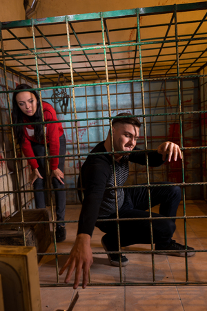 imprisoned: Two young victims imprisoned in a metal cage with a blood splattered wall behind them, boy pulling his hand through the bars and trying to get out Stock Photo