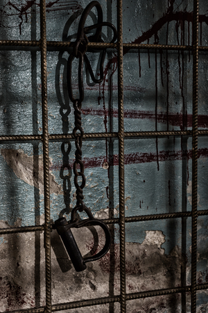 maniacal: Shackles hanging from chains on prison bar behind blood splattered wall for concept about torture or scary Halloween theme