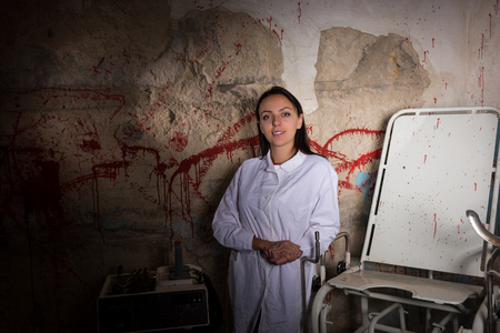 ghoulish: Smiling woman scientist in front of a blood splattered wall, Halloween concept