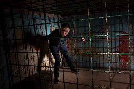 grisly: Man imprisoned in a metal cage with a blood splattered wall behind him shackled for concept about torture or scary Halloween theme