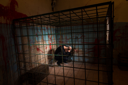 imprisoned: Male imprisoned in a metal cage with a blood splattered wall behind him shackled and sitting in the corner for concept about torture or scary Halloween theme