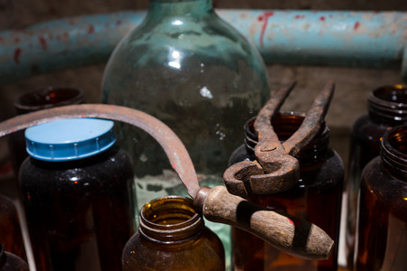 grisly: Glass jars, sickle and tongs with blood spattered wall in stained laboratory with glass case in a Halloween horror concept