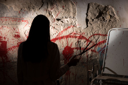 shadowy: Shadowy female figure holding iron scissors near blood stained wall for concept about murder and scary Halloween holiday
