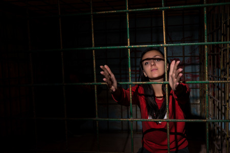 imprisoned: Young female victim imprisoned in a metal cage with a blood splattered wall behind reaching hands through bars Stock Photo