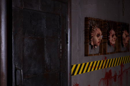 ghoulish: Big iron black door near ghastly faces stuck in square frames above yellow and black warning symbol and bloody wall in basement in a Halloween horror concept