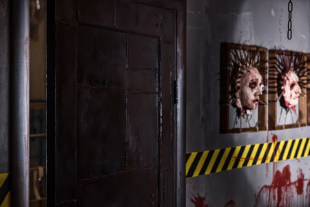 frightful: Frightful iron door near ghastly faces stuck in square frames above yellow and black warning symbol and bloody wall in basement in a Halloween horror concept