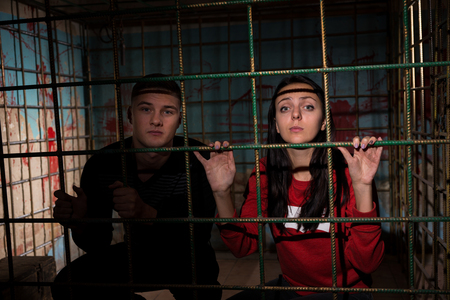 gory: Young female and male victims imprisoned in a metal cage with a blood splattered wall behind them holding bars