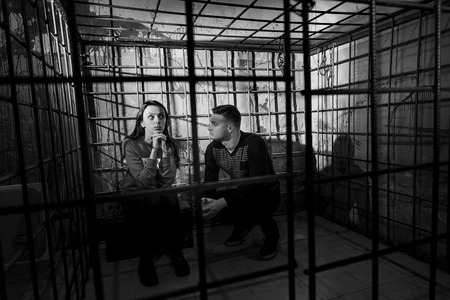 ghoulish: Black and white picture of two Halloween victims imprisoned in a metal cage with a blood splattered wall behind them sitting in terror awaiting their fate