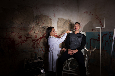 maniacal: Crazy scientist holding medical forceps in front of patient in dungeon with bloody walls in a Halloween horror concept