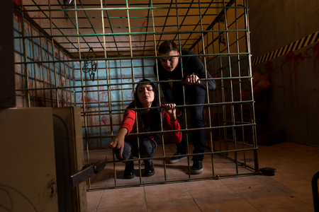 grisly: Two young Halloween victims imprisoned in a metal cage with a blood splattered wall behind them, girl pulling her hand through the bars and trying to get out Stock Photo