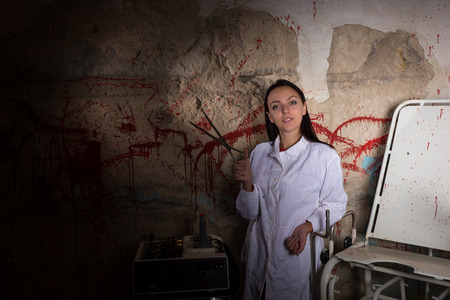 gory: Female scientist holding large iron scissors in dungeon with bloody walls in a Halloween horror concept