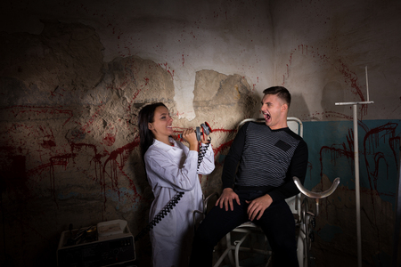 maniacal: Demented female scientist holding electrical shocking devices in front of patient in dungeon with bloody walls in a Halloween horror concept Stock Photo