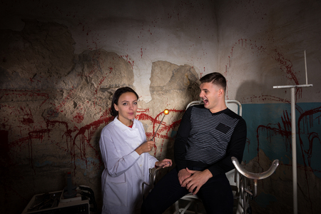 dungeon: Demented scientist holding iron medical heated device in front of screaming patient in dungeon with bloody walls in a Halloween horror concept