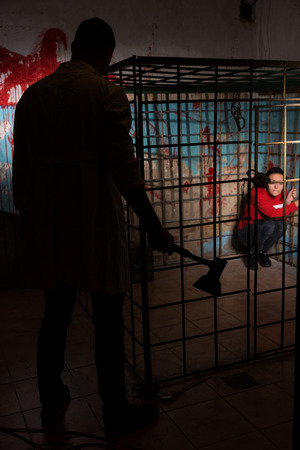grisly: Shadowy male figure holding an ax in front of victim imprisoned in a metal cage with a blood splattered wall behind her sitting in terror awaiting a fate
