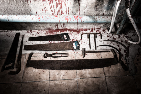 maniacal: Saws, sickles, tongs and other devices on the bloody floor  in basement with pipes and wires in a Halloween horror concept