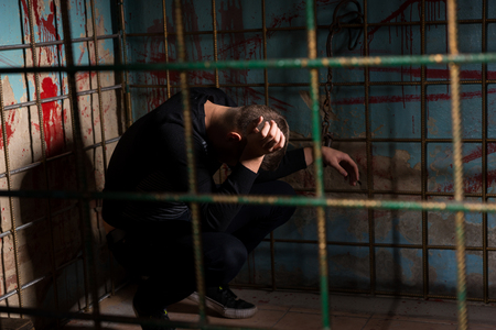 imprisoned: Male victim imprisoned in a metal cage with a blood splattered wall behind him shackled for concept about torture or scary Halloween theme