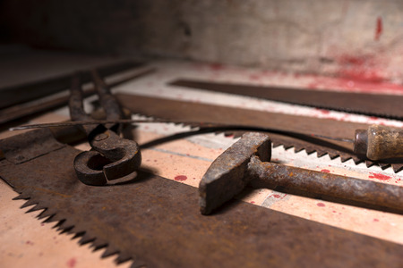 maniacal: Close up of saws, sickles and other devices on the bloody floor in basement in a Halloween horror concept