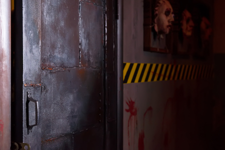 grisly: Open iron black door near ghastly faces stuck in square frames above yellow and black warning symbol and bloody wall in basement in a Halloween horror concept Stock Photo
