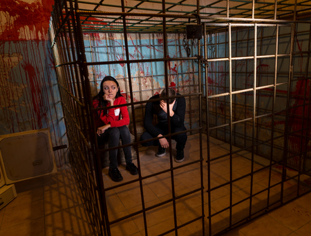 imprisoned: Two scared Halloween victims imprisoned in a metal cage with a blood splattered wall behind them sitting in terror awaiting their fate Stock Photo