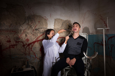 maniacal: Female madness scientist holding medical forceps in front of patient and tries to cut off the tongue in dungeon with bloody walls in a Halloween horror concept