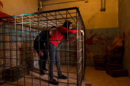 imprisoned: Two Halloween victims imprisoned in a metal cage with a blood splattered wall behind them trying to get out