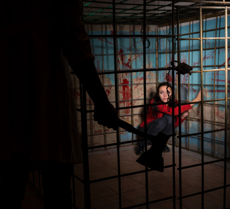 imprisoned: Shadowy male figure holding an ax in front of female victim imprisoned in a metal cage with a blood splattered wall behind her sitting in terror awaiting a fate Stock Photo