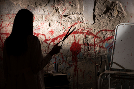grisly: Shadowy female figure holding scissors near blood stained wall for concept about murder and scary Halloween holiday