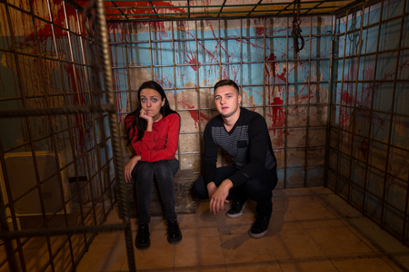 fate: Couple of Halloween victims imprisoned in a metal cage with a blood splattered wall behind them sitting in terror awaiting their fate