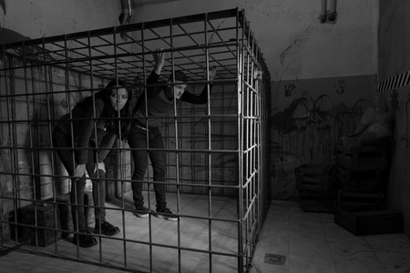 imprisoned: Black and white picture of victims imprisoned in a metal cage with a blood splattered wall behind them trying to get out