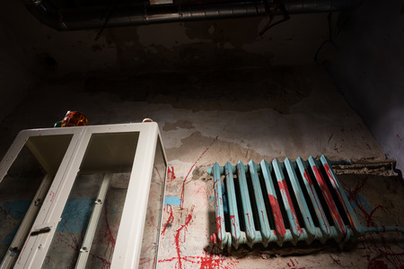 Bloodied battery near glass case in dimly lit basement in a Halloween horror concept