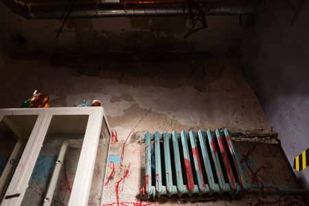 dimly: Terrible bloodied battery near glass case in dimly lit basement in a Halloween horror concept Stock Photo