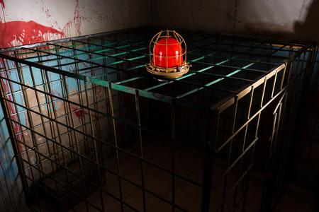 maniacal: Red lamp on the iron cage behind blood splattered wall for concept about scary Halloween theme