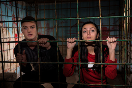 fate: Young female and male victims imprisoned in a metal cage with a blood splattered wall behind them sitting in terror awaiting a fate Stock Photo