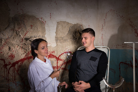 maniacal: Demented scientist holding iron sparkling medical device in front of patient in dungeon with bloody walls in a Halloween horror concept Stock Photo