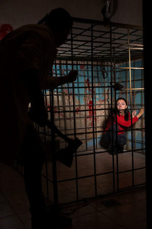 fate: Shadowy male figure holding an ax in front of afraid girl imprisoned in a metal cage with a blood splattered wall behind her sitting in terror awaiting a fate