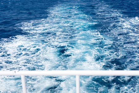 View of ships wake from the yacht through handrail Stock Photo