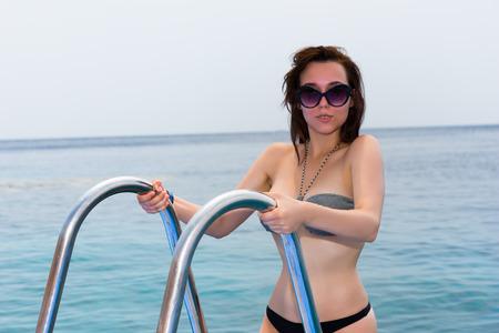 bajando escaleras: Mujer en bikini de gafas de sol se va por las escaleras abajo en el mar Foto de archivo