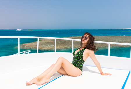 Beautiful female in black-green swimsuit lying on the deck of the yacht at a sunny summer day, breeze developing hair, beautiful sea on background