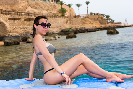 Female sitting on pontoon in front of the beautiful and clean sea after swimming
