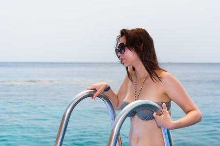 bajando escaleras: La mujer joven en gafas de sol que lleva el bikini está bajando las escaleras abajo en el mar