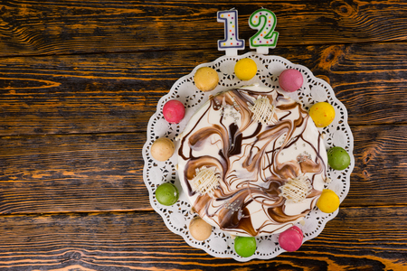 sweet seventeen: Cake for new year and christmas on wooden background, near candles number 12, new year concept